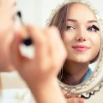 Beauty model teenage girl looking in the mirror and applying mascara make up. Beautiful young woman apply makeup