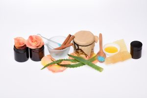 Homemade cosmetics with natural ingredients aloe vera honey cashew almond cinnamon in mortar black plastic containers with rose petals and blue bath salt in spoon isolated on white background