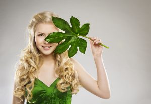Woman Face and Green Leaf Hair Organic Treatment and Skin Care Concept Young Girl with Long Blond Hairs over Gray Background